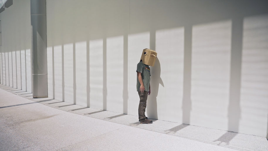 Still from the film Like Shadows Through Leaves, 2021. A figure stands next to a minimalist wall wearing a cardboard bird mask