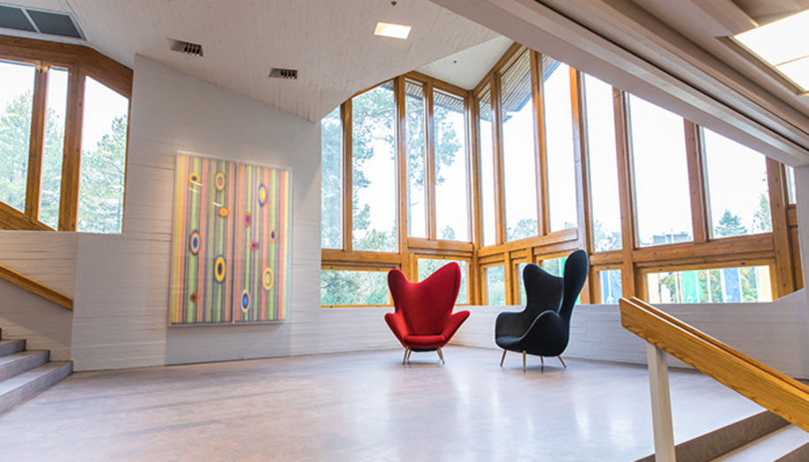 Two armchairs and an acrylic painting by Hans-Christian Berg decorates a stairs landing in Dipoli, Aalto University
