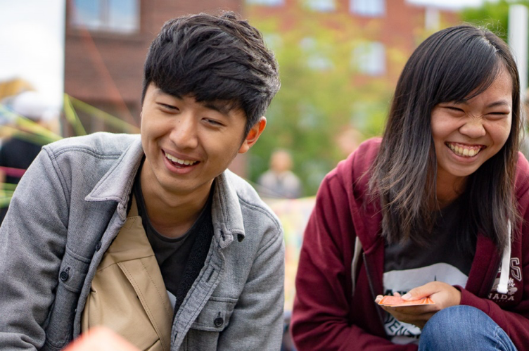 Two students laughing together.
