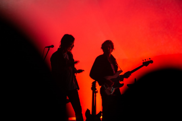 Tame Impala's and band member's black silhouettes against a red backdrop.
