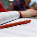 An Aalto pen lying on the page of a study book, students working in the background / photo by Aalto University, Aino Huovio