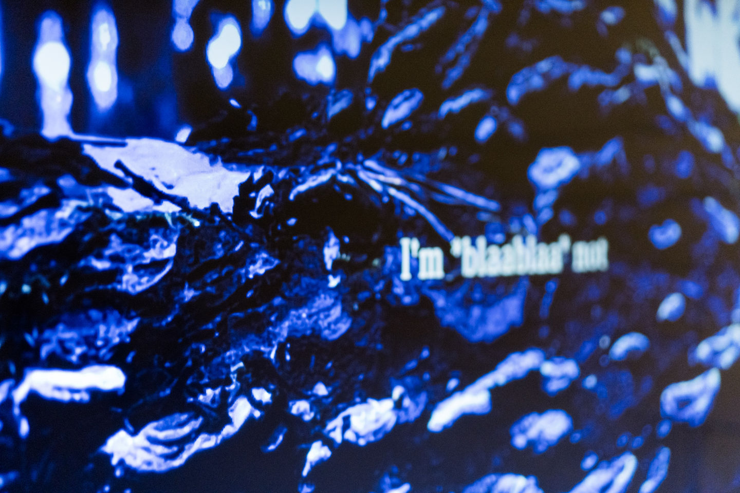 Close up of a digital piece showing swirls of blue and some fictional text laid over the top